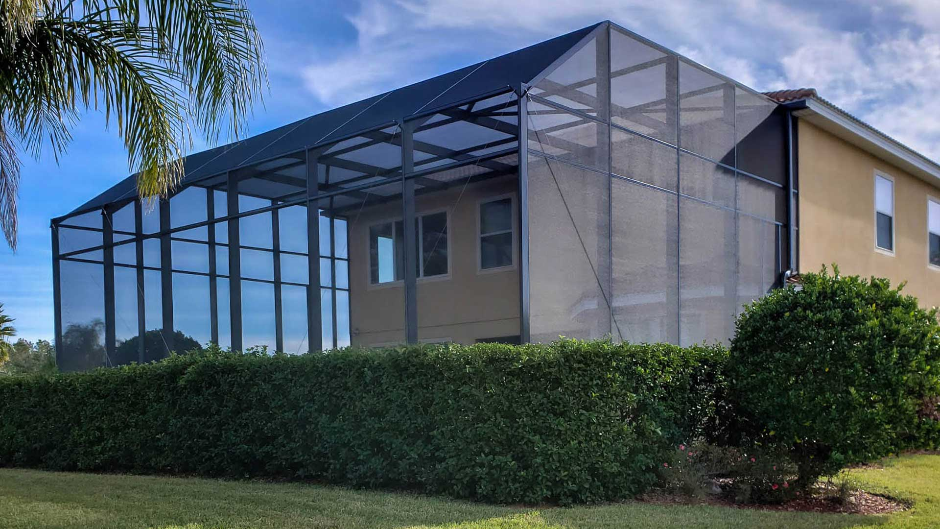 A two story screened lanai in the backyard of a residential property.